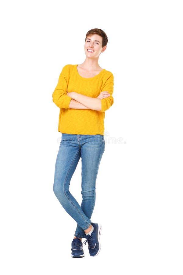 Condizione felice integrale della giovane donna con le armi attraversate contro fondo bianco isolato fotografia stock