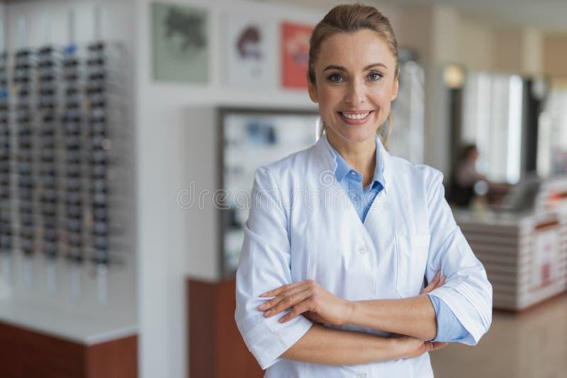 Condizione femminile allegra dell'ottico al deposito ottico immagine stock