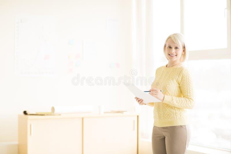 Condizione femminile con il documento in ufficio immagine stock