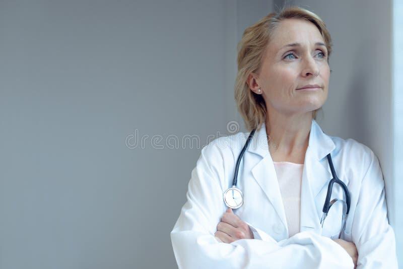Condizione femminile di medico con le armi attraversate nell'ospedale immagini stock