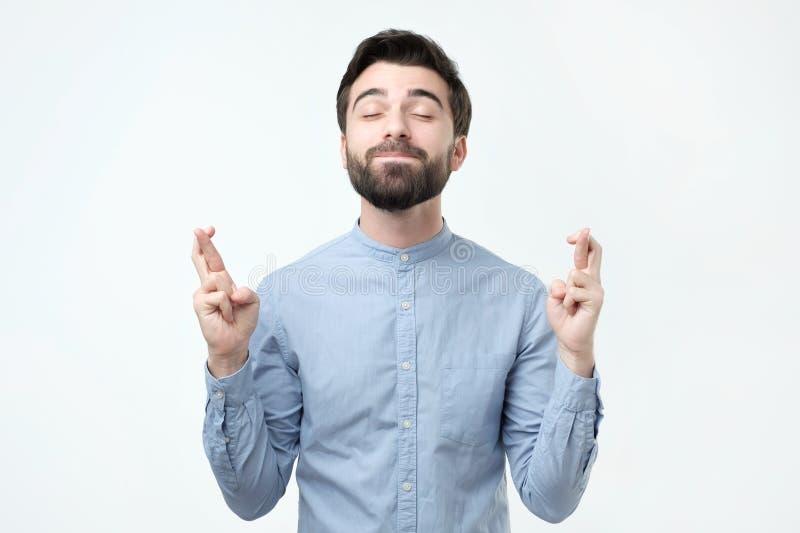 Condizione ispana dell'uomo con le dita attraversate e gli occhi chiusi, avendo supplica dell'espressione immagini stock libere da diritti