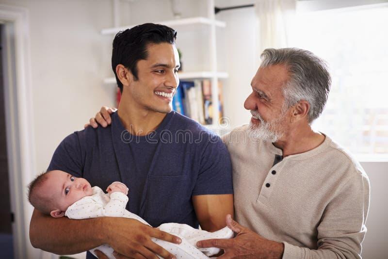 Condizione ispana senior fiera dell'uomo con suo figlio adulto che tiene il suo ragazzo di quattro mesi fotografia stock libera da diritti