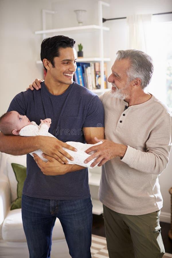 Condizione ispana senior fiera dell'uomo con suo figlio adulto che tiene il suo ragazzo di quattro mesi, verticale fotografia stock libera da diritti