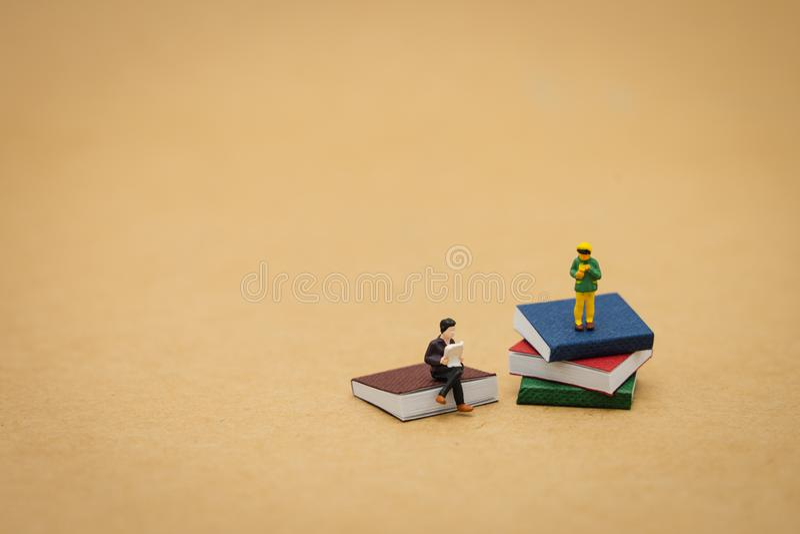 Condizione miniatura della gente dei bambini sui libri usando come concetto di istruzione del fondo ed imparando concetto con lo  immagini stock