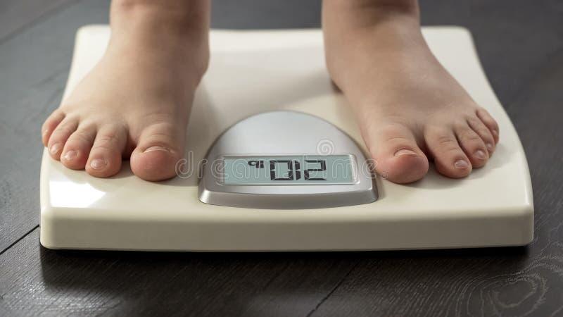 Condizione obesa della donna sulle scale per controllare il peso corporeo, problema di peso eccessivo, primo piano immagine stock