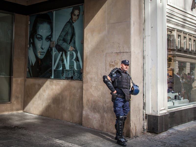Condizione serba del poliziotto davanti ad un deposito di modo con l'anti attrezzatura antisommossa nel centro di Belgrado, Serbi fotografia stock libera da diritti