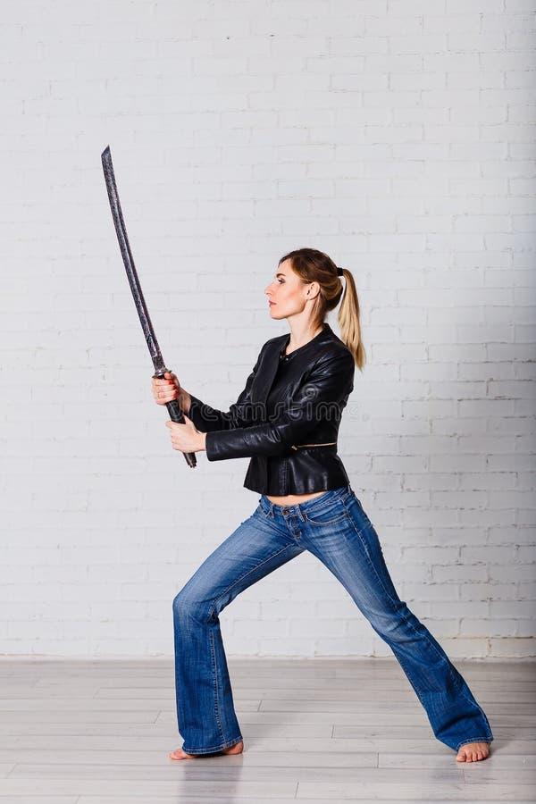 Condizione sexy della giovane donna nella posa del guerriero con la grande spada antica a disposizione fotografia stock libera da diritti