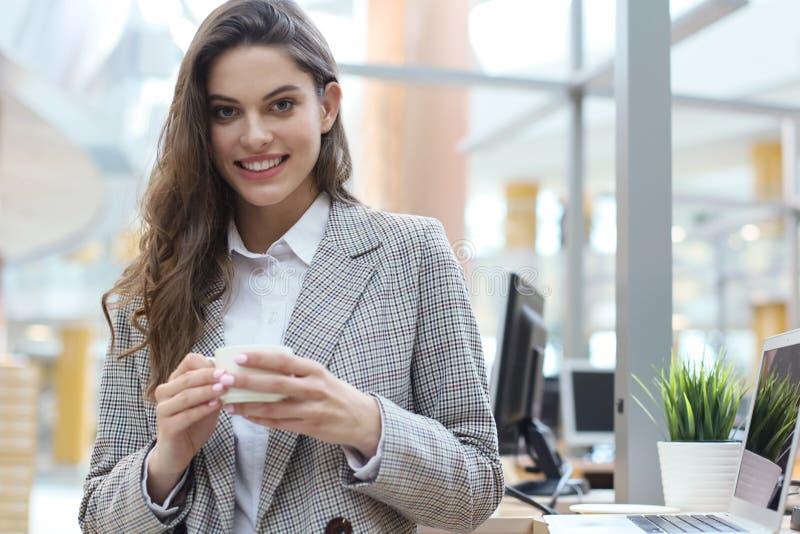 Condizione sorridente attraente della donna di affari nell'ufficio con una tazza di caffè fotografia stock libera da diritti