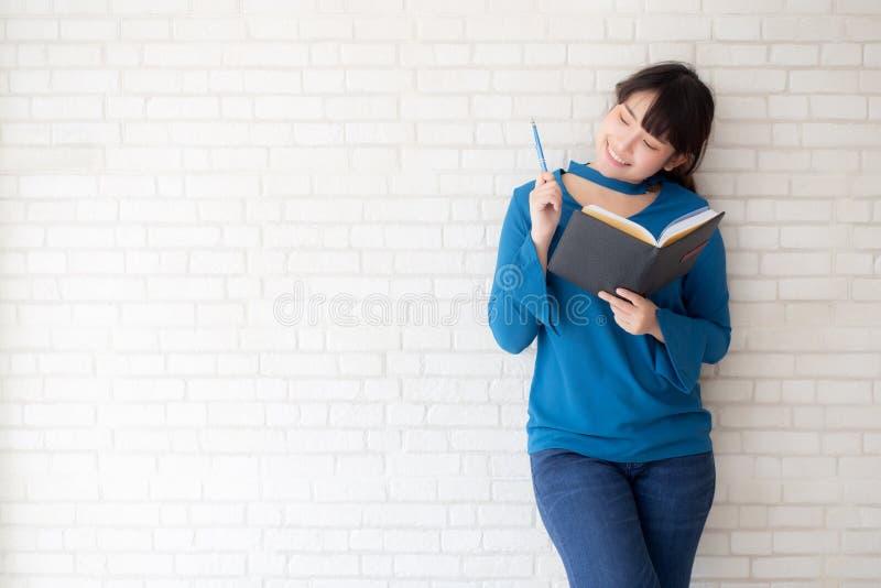 Condizione sorridente della bella donna asiatica che pensa e che scrive taccuino sul fondo bianco del cemento concreto a casa fotografie stock libere da diritti