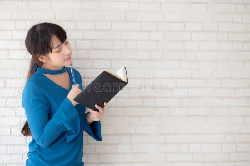 Condizione sorridente della bella donna asiatica che pensa e che scrive taccuino sul fondo bianco del cemento concreto a casa immagine stock libera da diritti