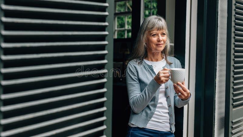 Condizione sorridente della donna anziana alla porta con una tazza di caffè a disposizione Donna senior che gode di una condizion immagini stock