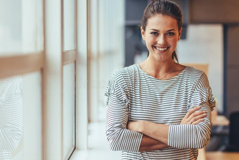 Condizione sorridente della donna di affari con le armi attraversate immagine stock