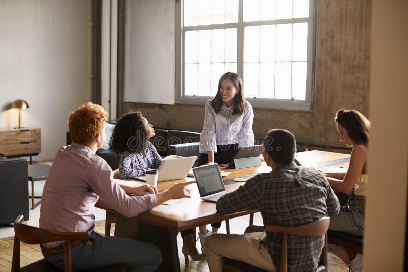 Condizione sorridente della donna per parlare ai colleghi ad una riunione del lavoro immagine stock libera da diritti