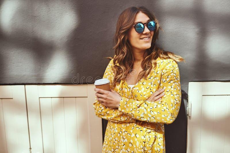 Condizione sorridente della giovane donna nella città che beve un caffè immagine stock libera da diritti