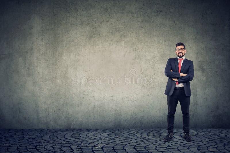 Condizione sorridente sicura dell'uomo di affari contro un fondo della parete fotografia stock libera da diritti