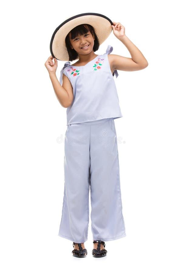 Condizione sveglia della bambina nell'usura di nuoto e cappello su fondo bianco fotografie stock libere da diritti