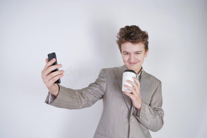 Condizione teenager emozionale divertente del ragazzo con la tazza di carta di t? e del selfie fare su fondo bianco da solo immagine stock