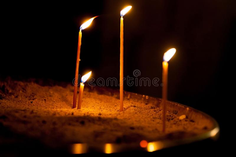 Condolence card. Remembrance day Mourning memorial funeral peace. Crematorium concept. Close up horizontal landscape four burning fired candles with orange royalty free stock photography
