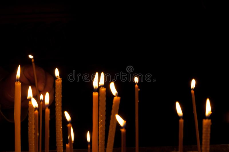 Condolence card. Remembrance day Mourning memorial funeral peace. Crematorium concept. Close up horizontal landscape plenty burning fired candles with orange royalty free stock photos