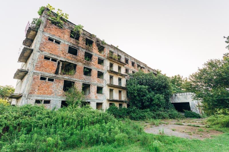 Condominio invaso rovinato con i segni della pallottola, conseguenze della guerra in Abkhazia, concetto post-apocalittico verde immagine stock