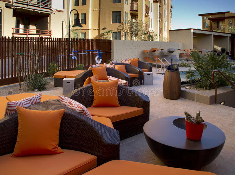 Condominium homes outdoor plaza patio and pool. Outdoor patio of an Arizona condominium project with a pool and bright orange cushioned patio furniture stock image