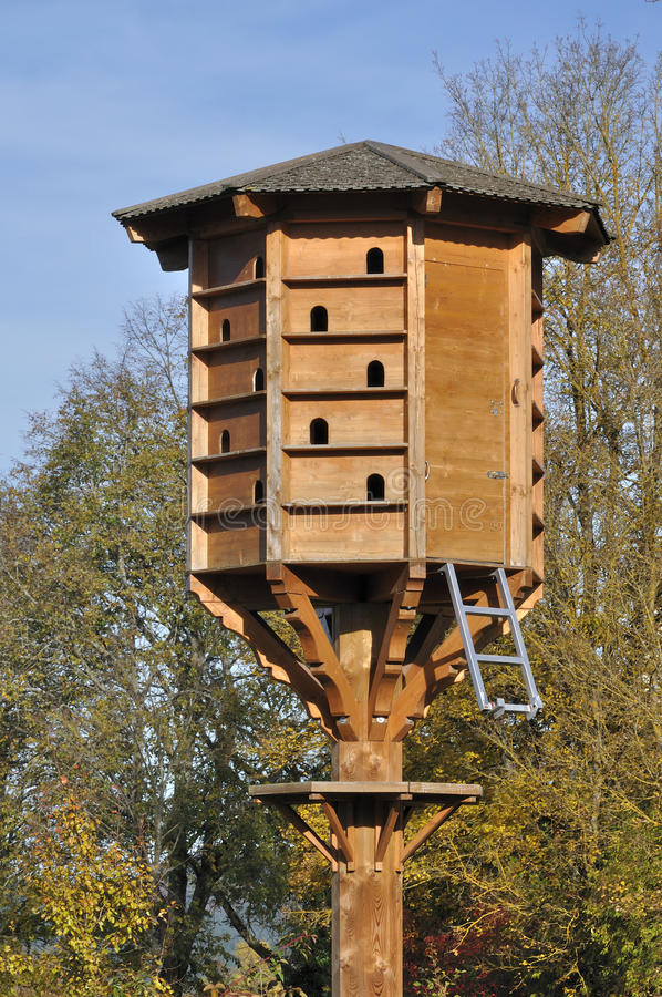 Condominium nest, rotwail. Big artificial nest in urban park, a wooden artificial apartment block for birds stock images