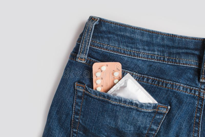 Condoms in package in jeans. Safe sex concept. Healthcare medicine, contraception and birth control. Close Up oral contraceptive pills. Protection against royalty free stock image