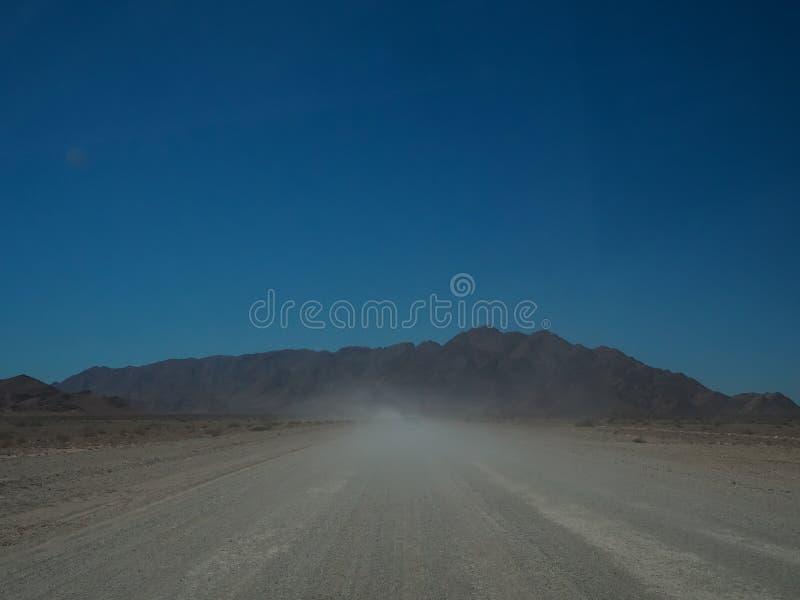 Condução através da estrada unpaved empoeirada à montanha rochosa entre o deser imagens de stock