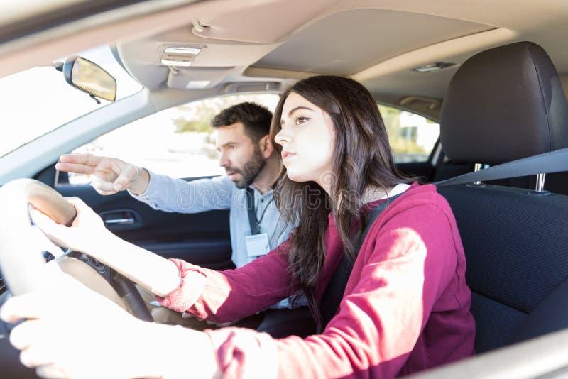 Condução de carro de Gesturing While Teaching do instrutor ao estudante imagem de stock