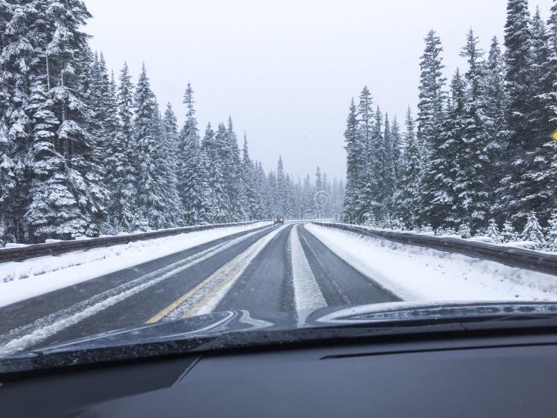 Condução de carro na estrada nevado coberto de neve da montanha na neve do inverno Ponto de vista do ponto de vista do ` s do mot imagens de stock
