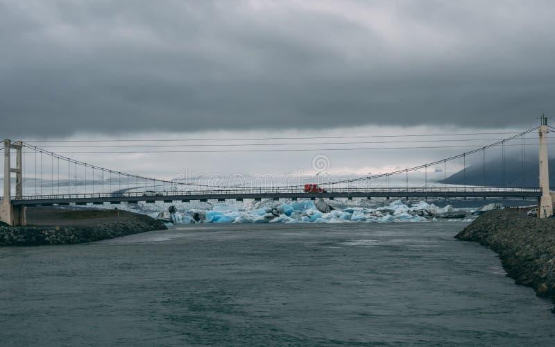 Condução de carro vermelha em uma ponte com a lagoa da geleira na parte traseira foto de stock royalty free