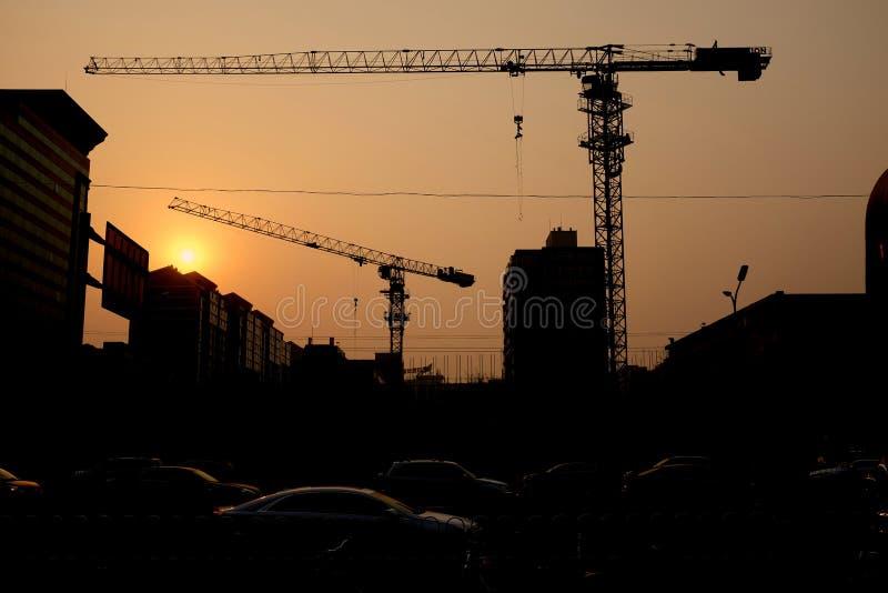 Condução de carros com o fundo de um canteiro de obras no crepúsculo, Pequim, China foto de stock royalty free