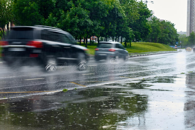 Condução de carros sob a chuva imagem de stock