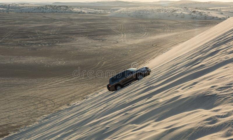 Condução de veículo 4WD acima de uma duna de areia no deserto de Khor Al Adaid em Catar imagens de stock royalty free