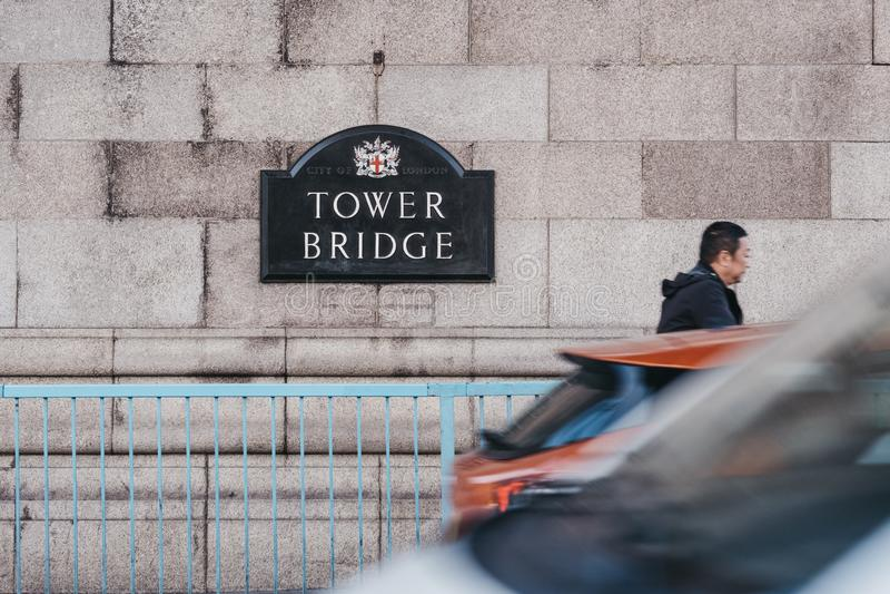 Condução e homem de carros que andam após o sinal do nome na ponte da torre, Londres, Reino Unido foto de stock royalty free