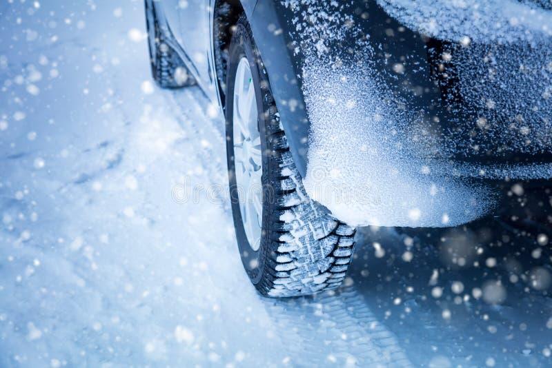 Condução no inverno - pneumáticos e queda de neve do ` s do carro imagens de stock