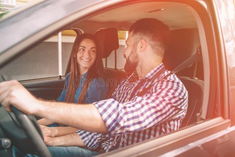 Conducción cuidadosa Pares jovenes hermosos que se sientan en los asientos de pasajero delanteros y que sonríen mientras que homb imagenes de archivo