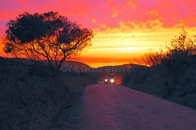 Conducción de automóviles en un camino de tierra en el oeste foto de archivo