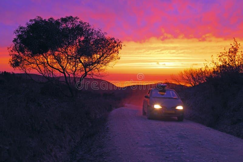 Conducción de automóviles en un camino de tierra en la puesta del sol imagen de archivo libre de regalías