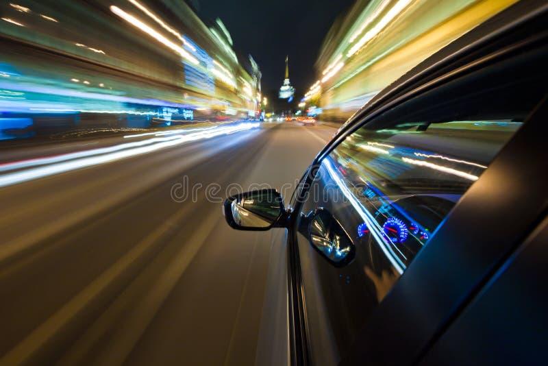 Conducción de automóviles rápidamente en la ciudad de la noche imágenes de archivo libres de regalías