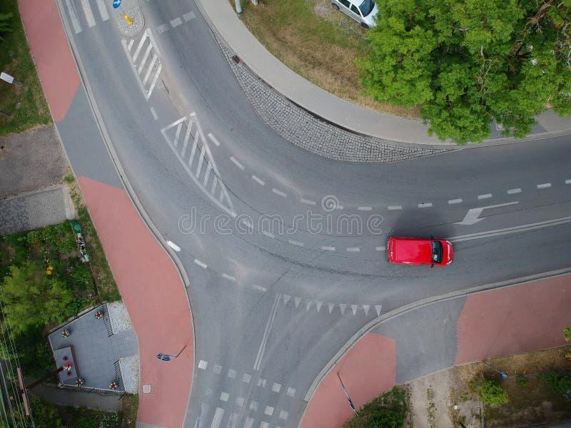 Conducción de automóviles roja a través de la intersección curvada en ciudad, visión aérea foto de archivo libre de regalías