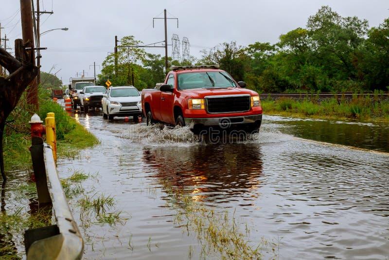 Conducción de automóviles a través del agua de inundación el camino durante la estación de la monzón fotografía de archivo libre de regalías