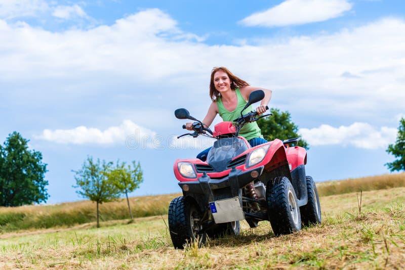 Conducción de la mujer campo a través con la bici del patio o ATV fotos de archivo
