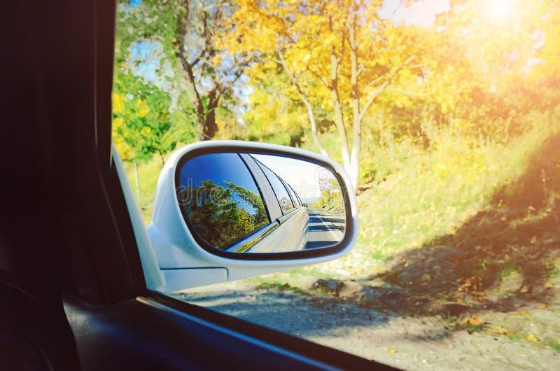 Conducción de un coche en el camino del otoño foto de archivo