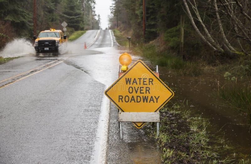Conducción de vehículo de la emergencia a través del agua en el camino inundado imagen de archivo libre de regalías