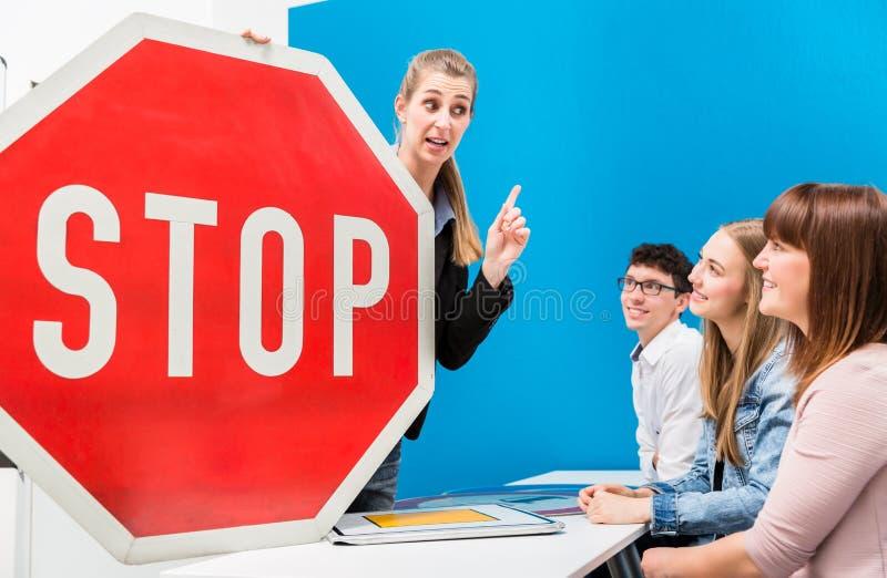 Conducción del profesor que explica el significado de placas de calle de clasificar foto de archivo