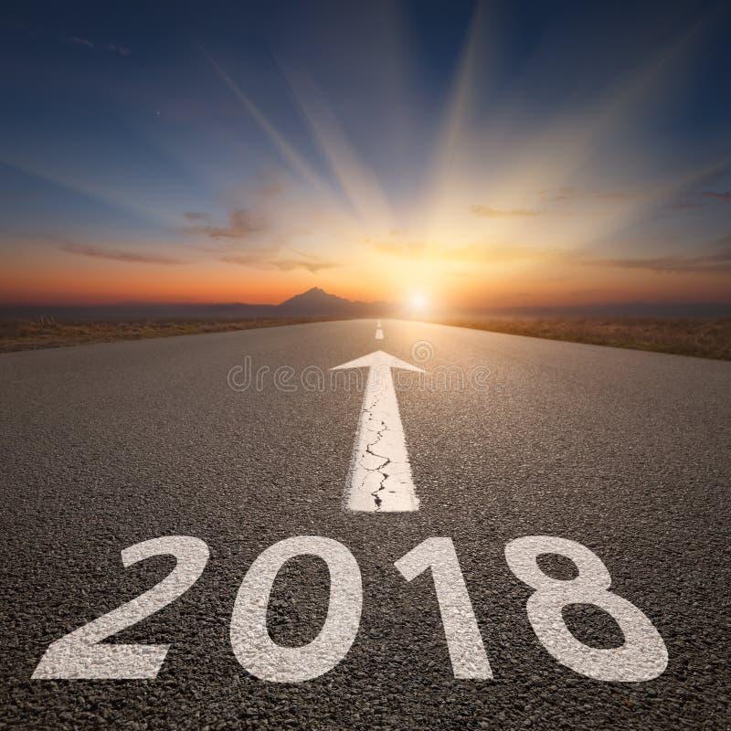 Conducción en el camino abierto hacia el 2018 en el amanecer foto de archivo libre de regalías