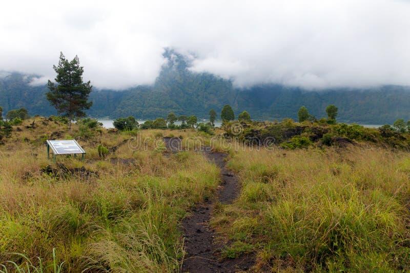 Conducción a través del camino del canto de la caldera entre vista del cráter extinto del volcán Batur fotos de archivo
