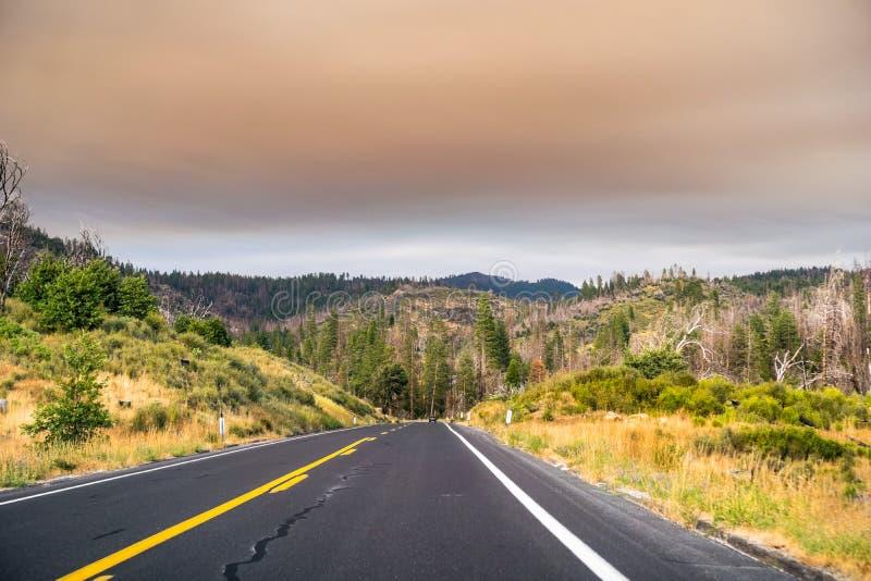 Conducción a través del parque nacional de Yosemite; cielo cubierto por el humo imagen de archivo