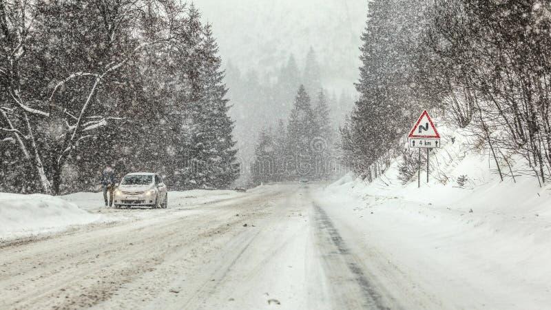 Conduciendo a través de ventisca pesada de la nevada en el camino forestal, las curvas amonestadoras a continuación para firmar a imagenes de archivo